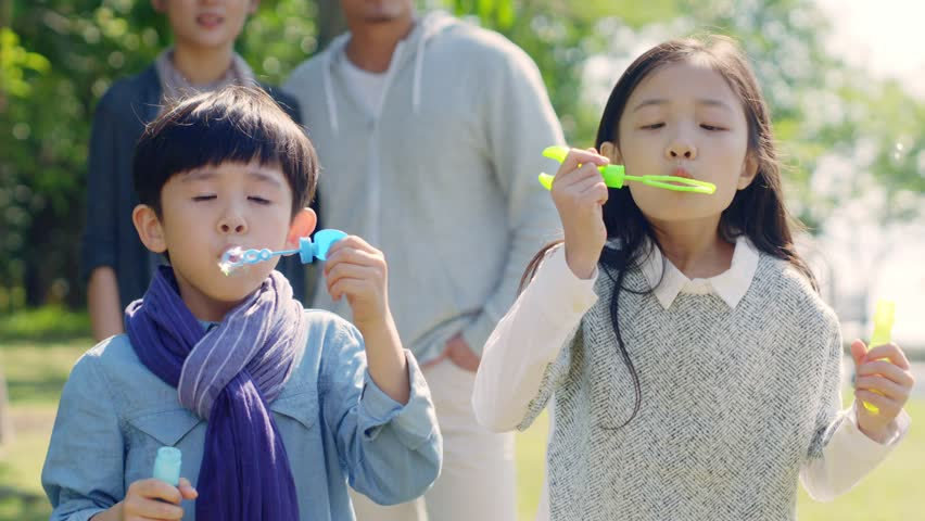 Two little asian children boy and girl playing outdoors blowing soap bubbles with parents watching from behind.