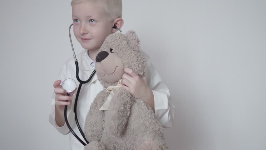 Cute boy in a doctor's lab coat listening to a teddy bear with a stethoscope. He plays doctors, educational games with children.