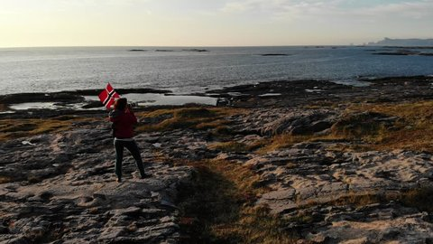 Aerial view. Tourist woman with waving norwegian flag enjoying sea coast view on rest stop area on Andoya island near Nordmela village Vesteralen archipelago, Norway