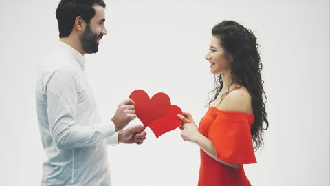608731e44f Young man and woman with arms around each other holding Valentines Hearts  while smiling for the