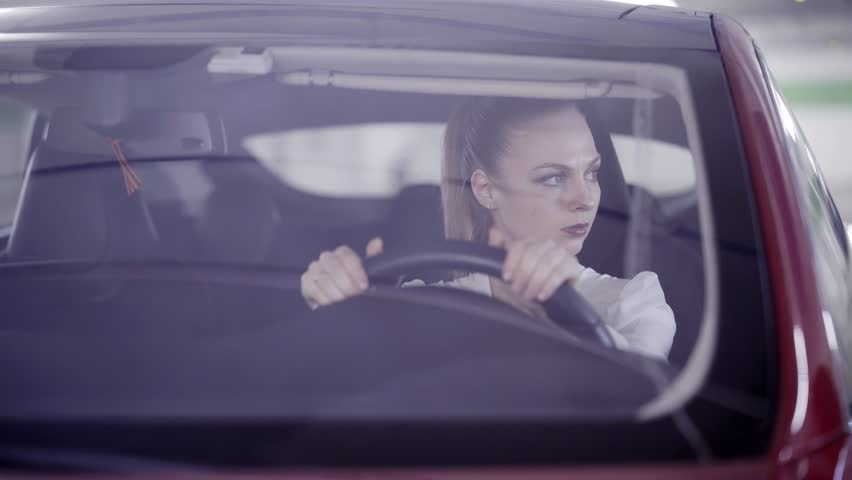 Nice young blonde girl with pony tail wearing white classic shirt is sitting in dark red car behind steering wheel when it's starts smoking outside in underground garage.