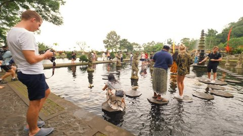 Tourists Taking Photos at Tirta Gangga - Famous Hindu Balinese Water Palace with Statues of the Gods and Pools Beautiful Fountains. 4K. 20 JAN 2019 - Bali, Indonesia.