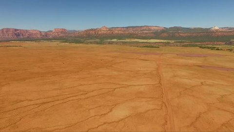 Aerial view of a dry land full of crevices with the Zion National Park in the background.