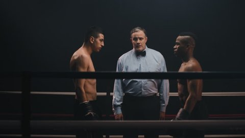 Two boxing rivals come together in a ring before a match. The referee explains the rules. They touch gloves and begin.