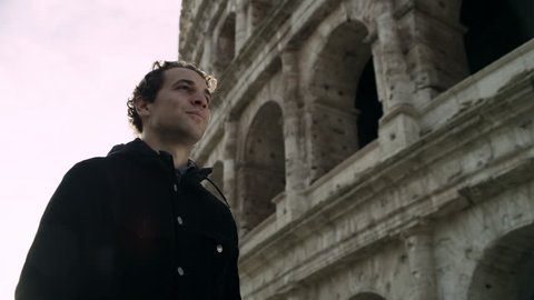 Happy, cheerful Italian man walking and looking up at the Coliseum, with soft natural light. Medium shot on 4k RED camera.