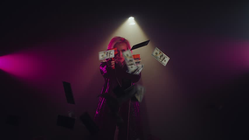 Sexual strong woman in dark long leather jacket posing with cash cannons. Edgy girl shooting lots of a money indoor. Shoot with RED RAVEN camera. | Shutterstock HD Video #1022772889