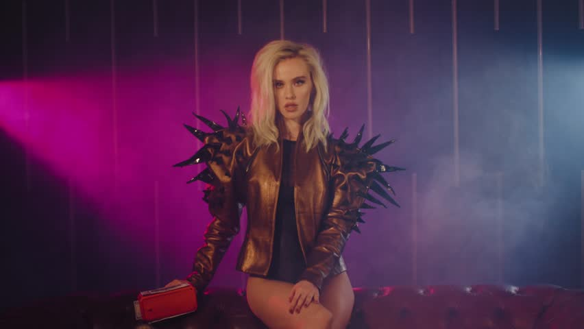 Fierce blonde rich woman sitting on a couch wearing jacket with stings and shooting money gun. Shoot with RED RAVEN camera. | Shutterstock HD Video #1022772949