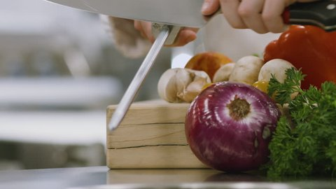 Close up, of chef sharpening knife in commercial kitchen with sharpening steel, cutting board and vegetables, soft focus background, clean and contemporary