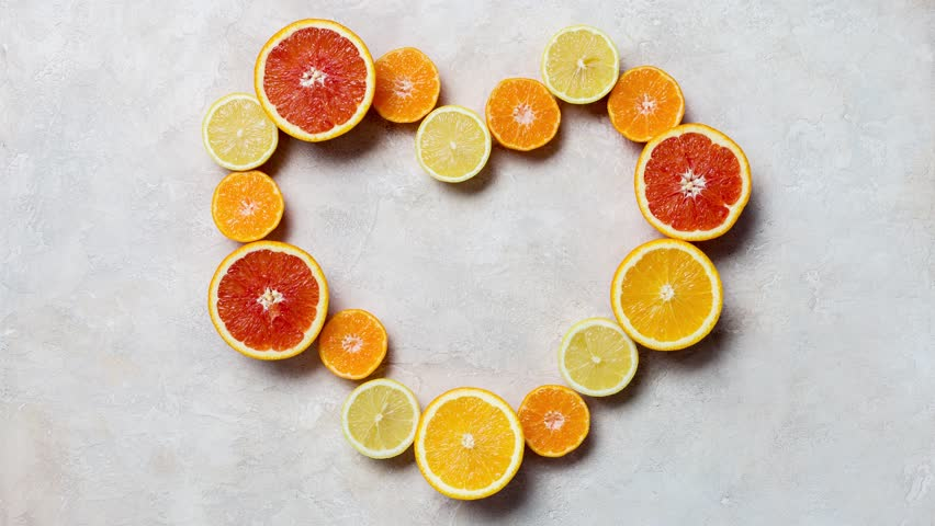 The heart of the citrus, orange, grapefruit, mandarin and lemon at white background. Time lapse background. Stopmotion of citrus heart shaped. Video background for Saint valentines day