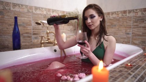 Beautiful woman pours red wine to glass but spills it into the water taking a bath with roses