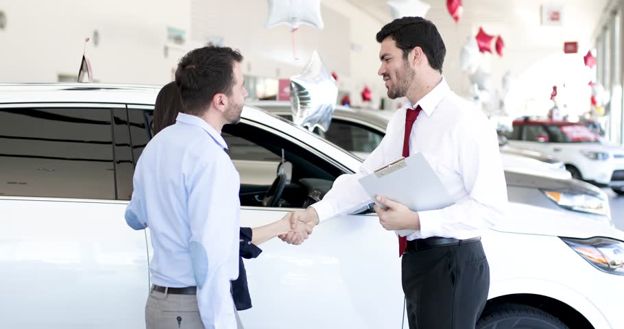 Good looking salesperson showing some cars to a couple in a car dealership