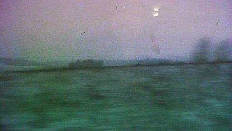 VHS effect over cinematic view through the window of a fast TGV ICE train over the French hills and villages early in the morning on the cold snowy winter - 4K UHD footage