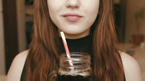 A young girl drinks a fizzy drink through a straw. Face close up. HD