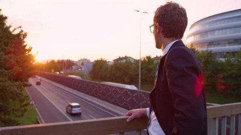 SLOW MOTION, LENS FLARE, CLOSE UP: Young Caucasian businessman lost in thought watches the busy highway below him at sunrise. Yuppie thinking about his stressful job while observing the golden sunset.