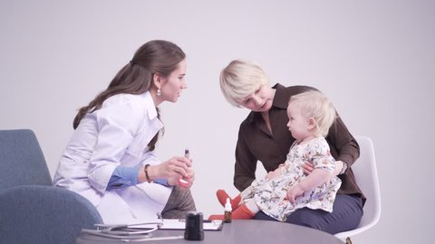 Blonde mother with 1 year old daughter at the doctor's office. medical checkup