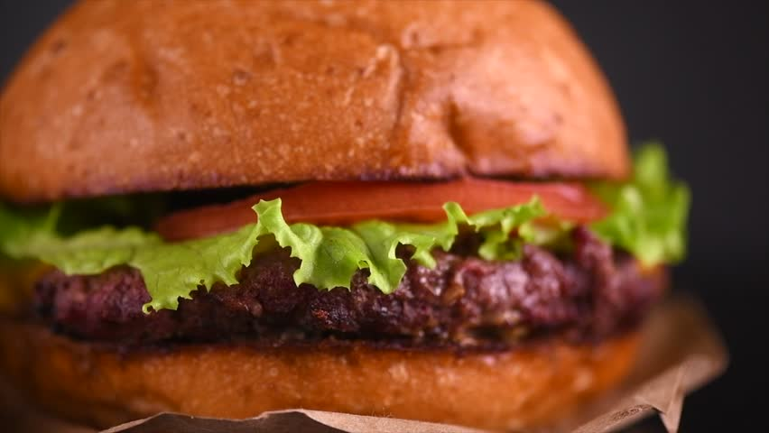 Hamburger with fries on black background. Cheeseburger on fresh buns with succulent beef and fresh salad ingredients on dark background. Slow motion 4K UHD | Shutterstock HD Video #1022929549