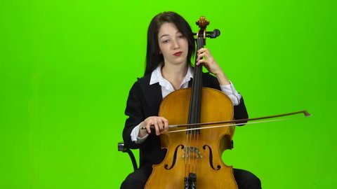Girl sits and plays the cello. Green screen