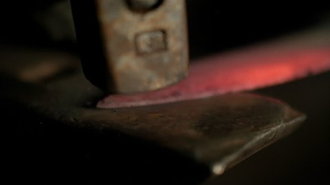 SLOW MOTION, MACRO, DOF: Glowing hot blade getting struck by a heavy hammer held by bladesmith. Cinematic detailed shot of unrecognizable craftsman forging a knife. Bright orange steel getting forged.