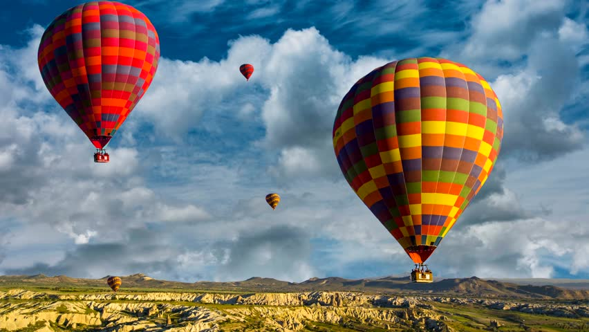 Cinemagraph of hot air balloons rising over the Cappadocia, Turkey desert amidst churning time lapse clouds.