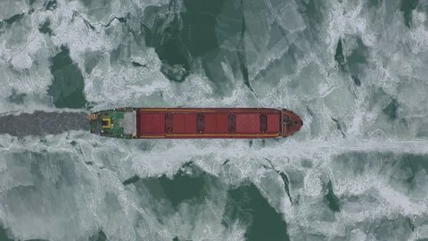 Cargo ship sailing on frozen sea in extreme winter conditions aerial shot. Sailing in narrow fairway channel made by icebreaker vessel. Water transportation during cold winter season in north.