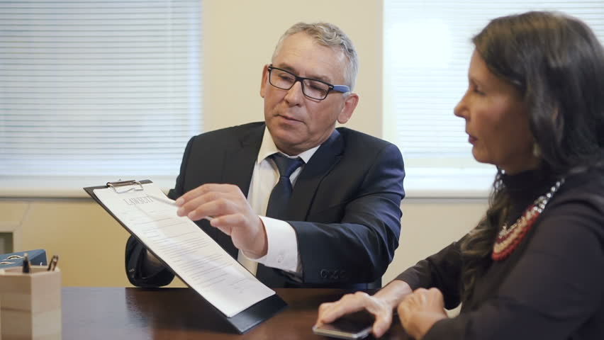 Senior legal expert explaining content of lawsuit to mature woman in office. Lawyer holding document and female witness reading it and listening before signing. Slow motion.
