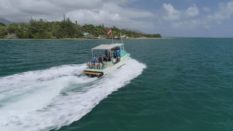 A wide,ing shot from the side of a small boat filled with tourists, speeding over the waters of Coconut Island, Kaneohe Bay, Hawaii, towards a tropical landscape