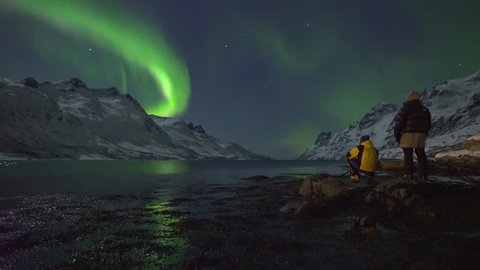 Northern Lights (Aurora Borealis) filmed in real time. Two tourists photographers take pictures and enjoy the calm display of green and purple colours, surrounded by mountains and arctic fjord