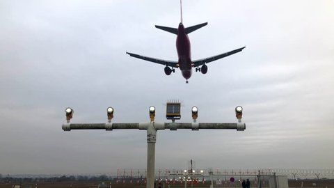 Airplane approaching the runway with landing lights and people watching