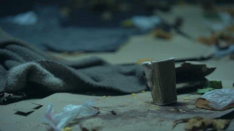 Drunk homeless woman lying down to sleep among garbage, alcohol addiction