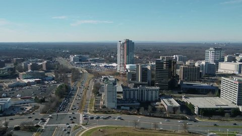 Tysons, VA / USA - December 29 2018: Aerial pan left to right across Tysons Corner skyline with International Drive in foreground