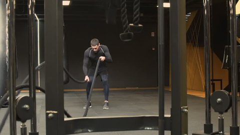 Athletic handsome young man with beard in black sportswear working out in gym using battle ropes. High-intensity interval training. Dolly shot, long shot. Training concept.