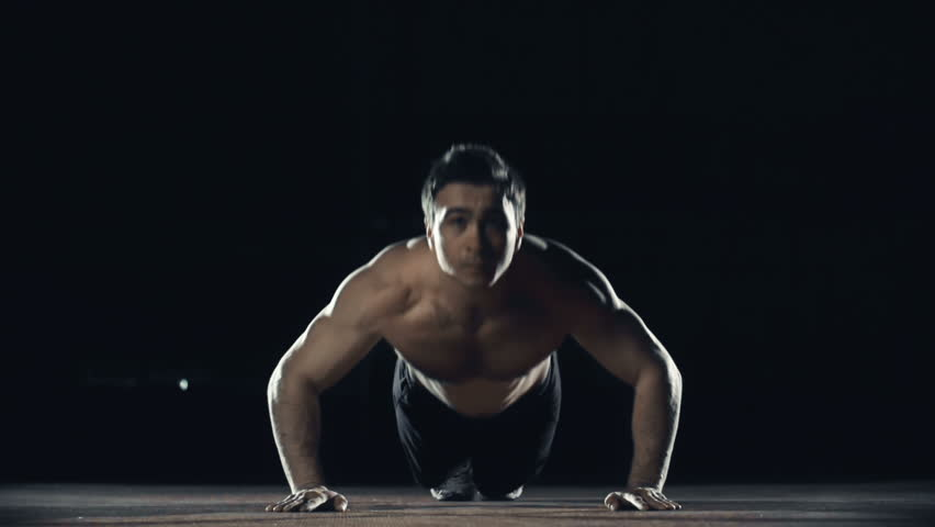 Front view of sportsman with naked torso performing explosive pushups clapping hands while in the air