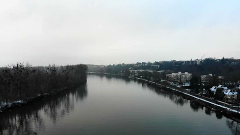 Aerial drone shot of the Seine river in winter with snow and a town