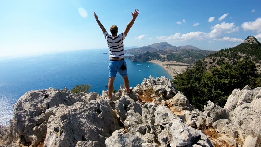 A young man reaching the top of the mountain and standing on cliff with arm raised. Mediterranean sea coast and rocks in the background