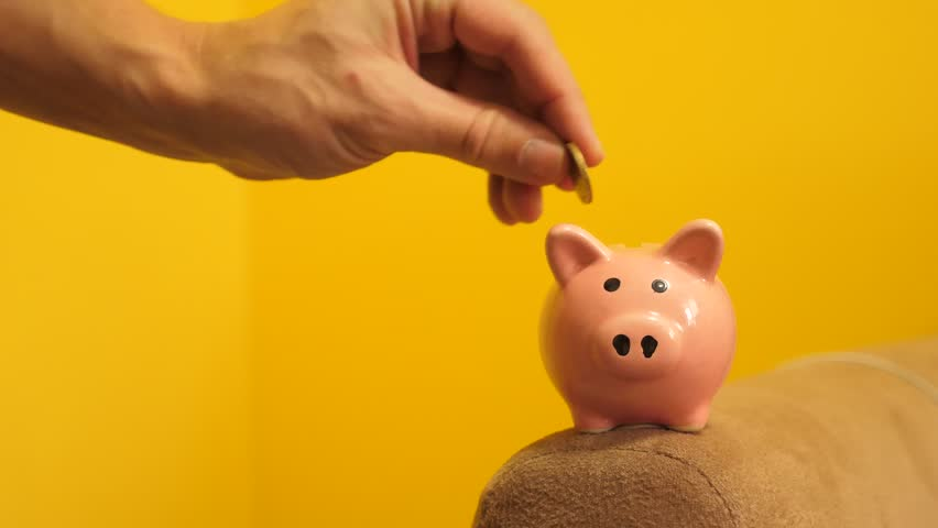 piggy bank business concept. A hand is putting lifestyle a coin in a piggy bank on a yellow background. saving money is an investment for the future. Banking investment and finance concept