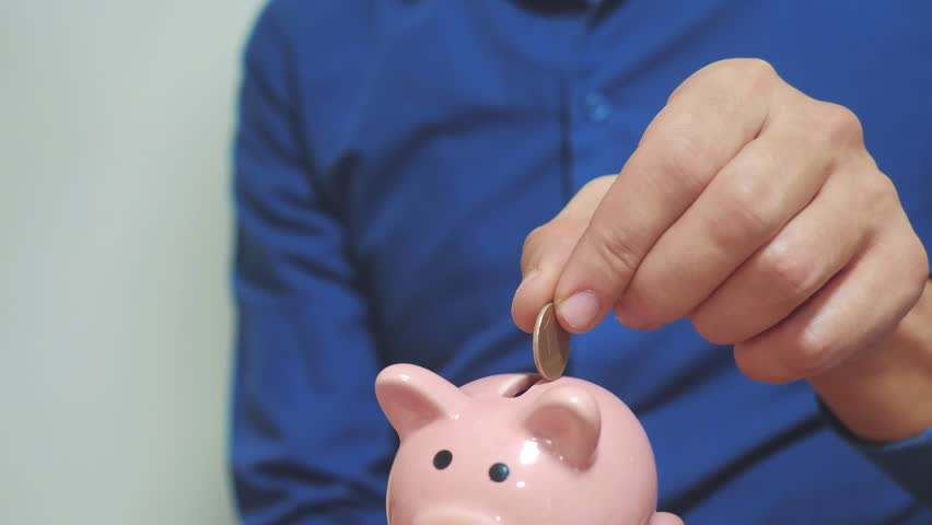two businessmen teamwork makes savings puts coins in a piggy bank. two men piggy bank business concept. slow motion video. saving money is an investment for the future. Banking investment lifestyle