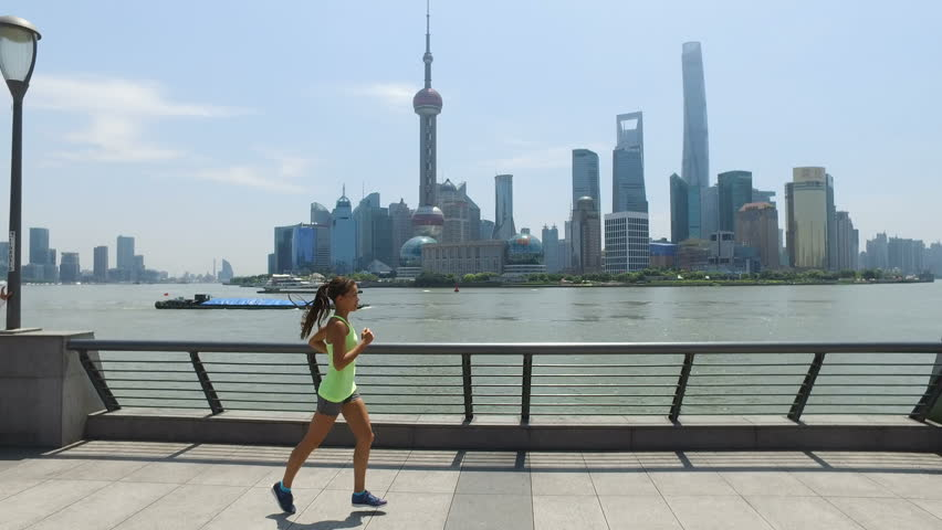 Asian woman running in city of Shanghai, China on famous boardwalk with skyline. Urban city lifestyle. Active woman runner exercising outside jogging on the Bund. Action camera | Shutterstock HD Video #1023169489