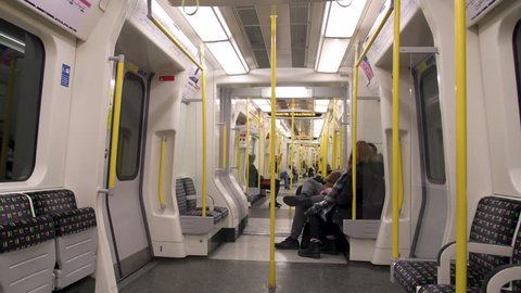 London, UK - January 29, 2019: Underground tube metro with interior inside subway train public transportation and people commuters sitting by empty seats