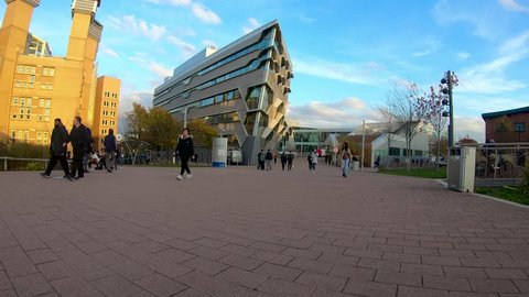Coventry, West Midlands, UK - November 6, 2018: Time lapse of Coventry university pedestrian area with the engineering building and library with students walking through