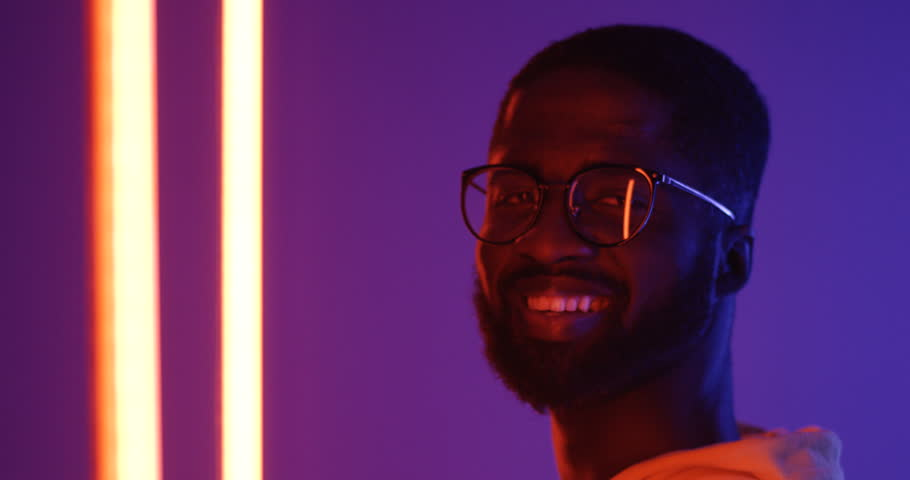 Close upof teh profile of the young African American man in glasses turning his head to the camera and smiling. Portrait. Neon lights. | Shutterstock HD Video #1023236869