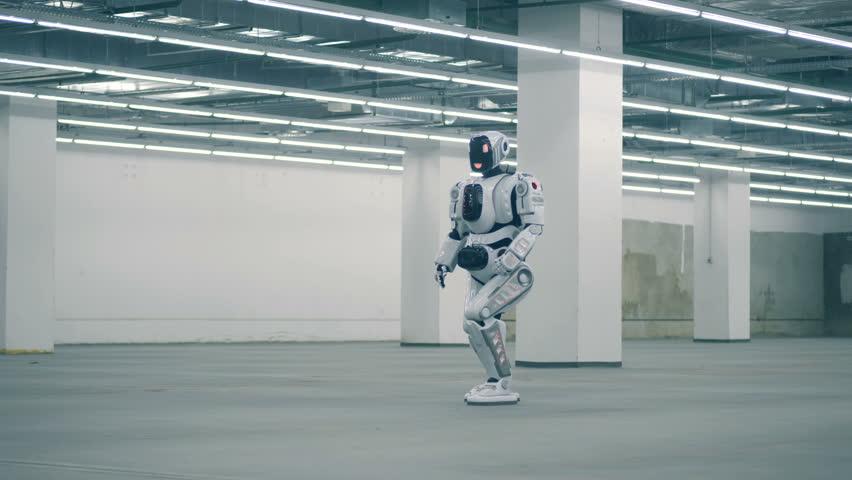 Human-like cybrog is walking along an empty storage unit | Shutterstock HD Video #1023238699