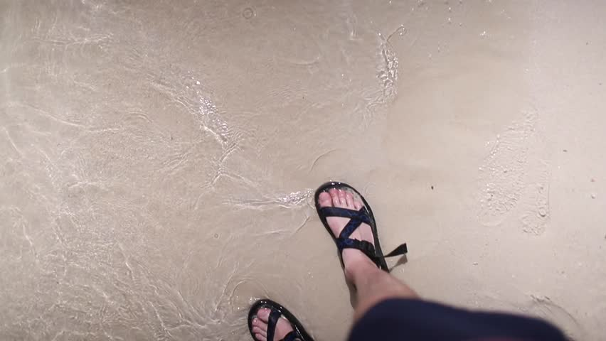 d75118b441d9 Person wearing sandals walking along beach with gentle waves splashing over  feet in sand.