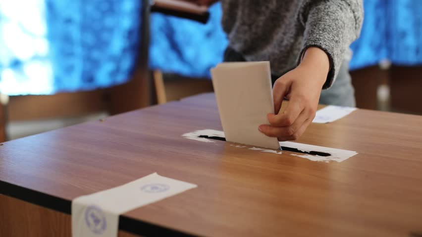 Video of a person casting a ballot at a polling station, during elections.