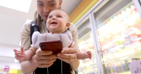 Happy young smiling mother with her little baby, glad to recieve text message on smart phone, loves her child, does shopping in supermarket. Motherhood and maternity concept