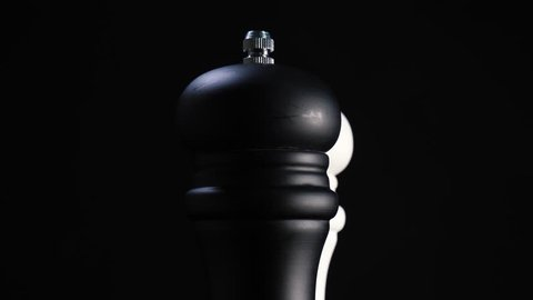 Camera dracking over two pepper mills with mixed pepper rotating against black background
