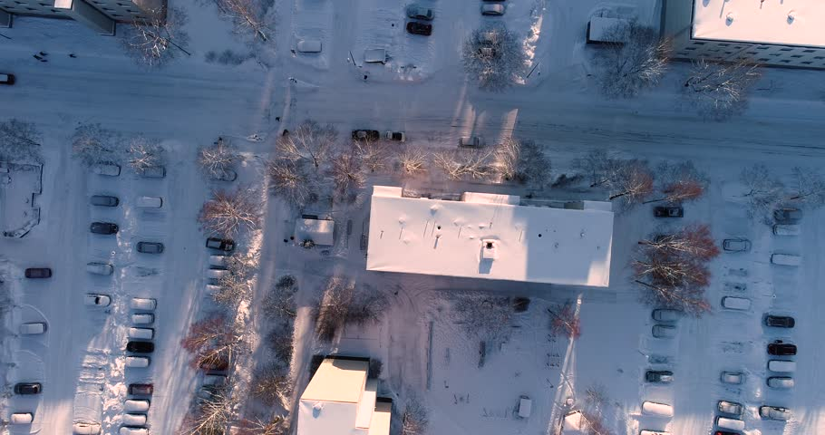 Winter and snow, flying over a street, apartment buildings and a parking with snow covered cars in the suburban of Espoo, Finland