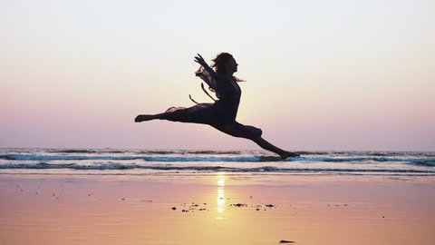 Silhouette of young woman performing grand jete jump on the beach at sunset in slow motion. Female ballet dancer jumping with twine at seashore.