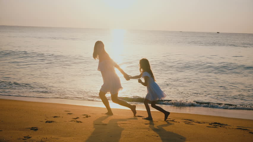 Happy beautiful young mother and little daughter running together holding hands, relaxing at epic sunset sea beach.