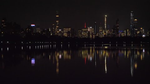 Manhattan Urban Cityscape and Reflection in Jacqueline Kennedy Onassis Reservoir in Central Park at Night. New York City. United States of America. Panning Shot