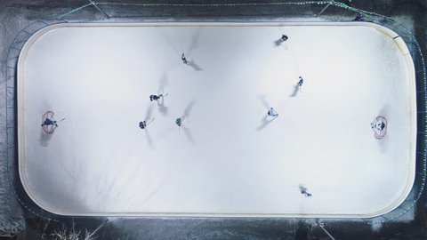 Playing Ice Hockey on Ice Rink. Aerial Vertical Top-Down View. Static Drone Shot